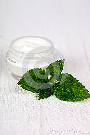 Face cream in glass jar with green leaf of urtica