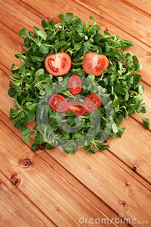 Face of fairytale character made out of mache lettuce and cherry tomatoes