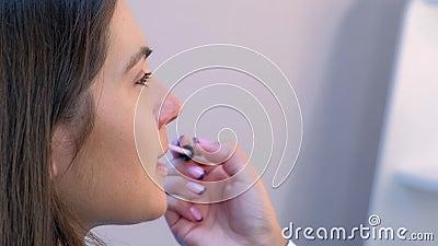 Face of girl moda modelka, która makijaż artysta tworzy szminkowy błysk wargi zdjęcie wideo