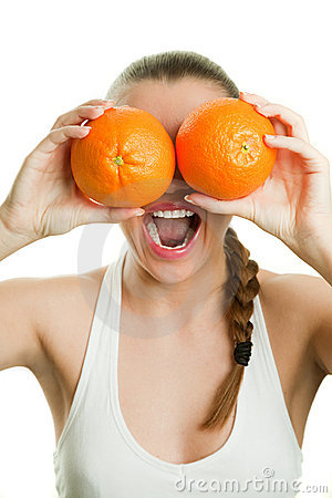 Face of joyful girl holding oranges by her eyes an