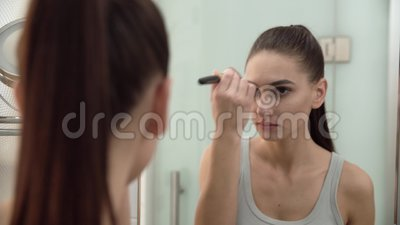 face makeup woman using powder and looking in mirror