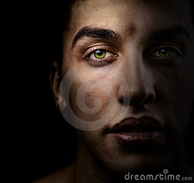Face of man in the dark with beautiful green eyes