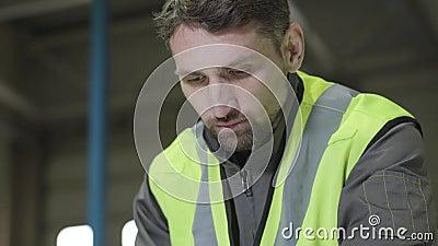 Face próxima de um homem caucasiano concentrado de olhos castanhos em colete verde olhando para baixo Trabalhador profissional no vídeos de arquivo