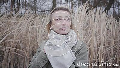 Face rapprochée d'une jeune belle femme caucasienne aux yeux bruns debout dans un vent froid Charmante blonde en attente banque de vidéos