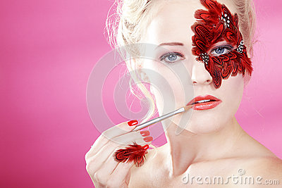 Face with red feathers and a lip brush