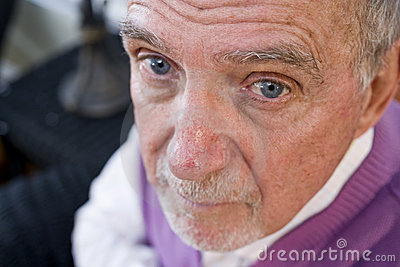 Face of serious elderly man staring at camera