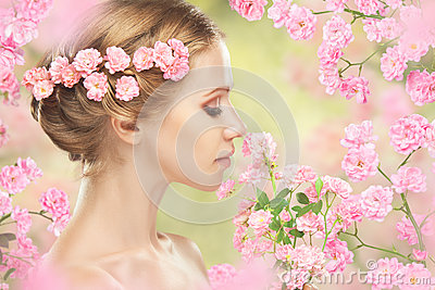 Face of young beautiful woman with pink flowers in her hair Stock Photo
