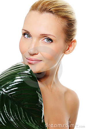 Face of a young health woman with the green leaf
