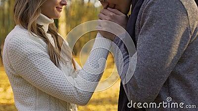Facet grże jego dziewczyn ręki i delikatnie całuje one, romantyczna atmosfera zdjęcie wideo