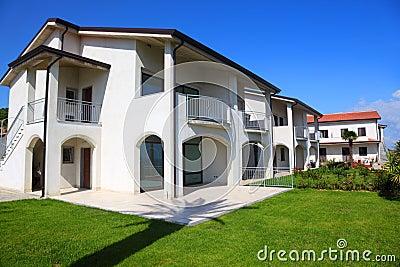 Fachada da casa de dois andares branca com jardim