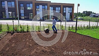 Fachowy pracownika mężczyzna ciągnie gazonu rolownika dla spłaszcza jard ziemię Gimbal ruch zbiory