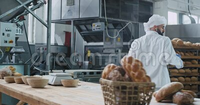 Factory food bakery dancing baker in the commercial kitchen listening music from wireless headphones and enjoying the. Time at work stock footage