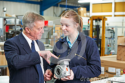 Factory Manager And Engineering Apprentice Discussing Component Stock Photo