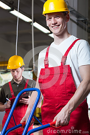 Factory workers pushing a manual trolley