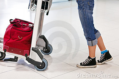 Fahrwerkbeine und Füße der Frau mit Gepäckauto