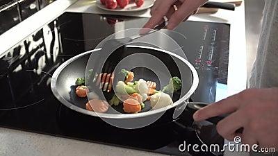 Faisant cuire des légumes sur faire frire Pan At Home Kitchen Closeup banque de vidéos