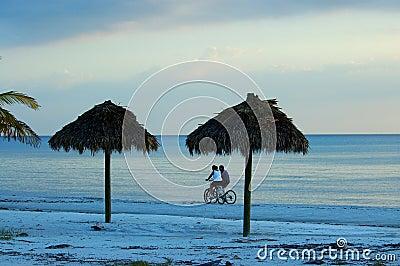 Faites du vélo les couples d équitation sur la plage de Fort Myers
