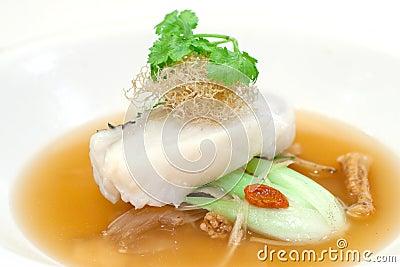 Faixa cozinhada do bacalhau em uma cama dos vegetais