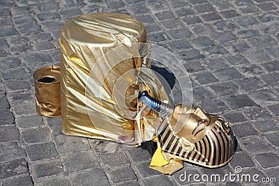 Fake golden mask pharaoh lies on pavement