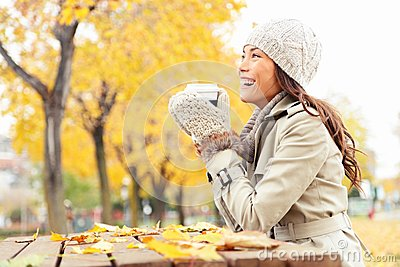 Fall concept - autumn woman drinking coffee