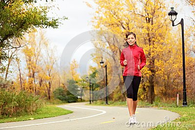 Fall running - woman jogging in autumn
