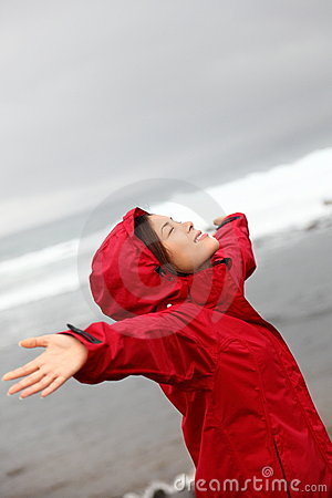 Fall woman in rain happy by nature ocean