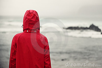 Fall woman in rain looking at ocean