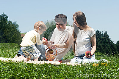 Família alegre que toma parte num piquenique