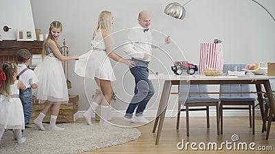 Família caucasiana animada dançando em torno de mesas dentro Pai sorridente, mãe, e três filhos segurando um ao outro filme
