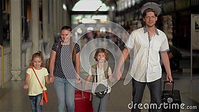 Família feliz com as crianças que vão na estação de trem, nos pais e nas crianças viajando e andando no aeroporto vídeos de arquivo