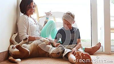 Família feliz da mãe e do filho no assoalho home com o cão amigável do lebreiro