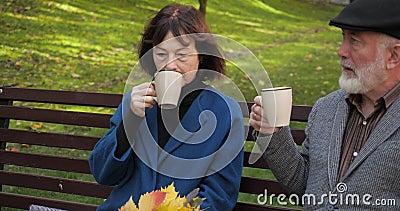 A família feliz está descansando em um banco num parque urbano aconchegante Idoso marido e mulher bebem chá no parque no outono filme