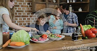 Família feliz na cozinha, pais que olham as crianças que cozinham o alimento que desbasta junto vegetais vídeos de arquivo