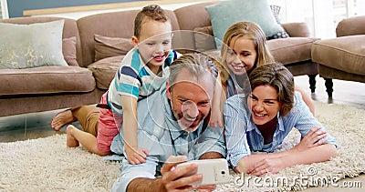 Família feliz no encontro no tapete e em falar um selfie no telefone celular vídeos de arquivo