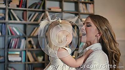 Família feliz - par novo que beija a filha mais nova do bebê, após o jogo com pinturas vídeos de arquivo