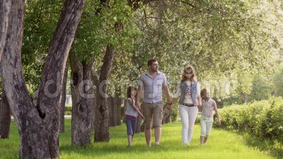 Família feliz que anda no parque do verão perto das árvores de Apple de florescência o pai, a mãe e duas filhas passam o tempo video estoque