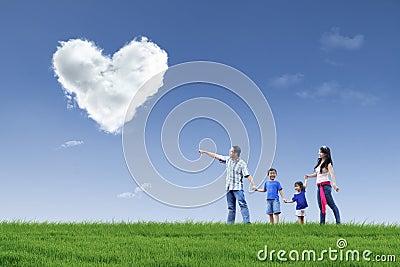 A família feliz vê nuvens do coração no parque