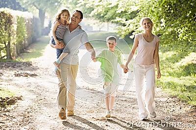 Família que anda ao ar livre prendendo as mãos e o sorriso
