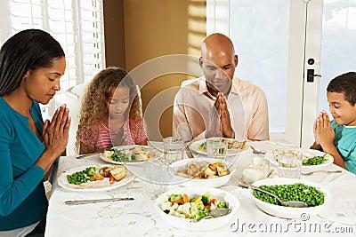 Família que diz a benevolência antes da refeição em casa