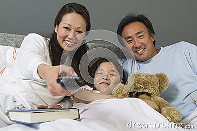 Família que olha a tevê junto na cama