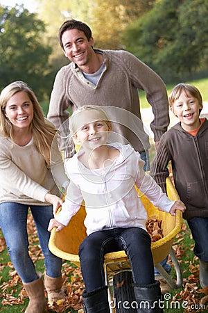 Família que tem o divertimento com as folhas de outono no jardim