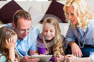 Famiglia che gioca con il calcolatore del ridurre in pani nel paese