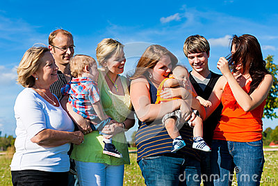 Famiglia e di diverse generazioni - divertimento sul prato di estate