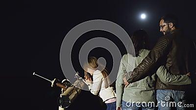 Famiglia felice che guarda la luna in un telescopio alla notte stock footage