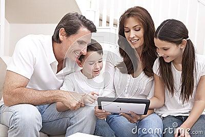 Famiglia felice che ha divertimento per mezzo del calcolatore del ridurre in pani