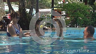 Famiglia felice degli europei che gioca con un bambino in una piscina ragazza e la donna che getta la piccola palla del bambino n stock footage