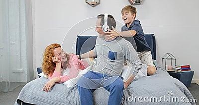 Famiglia felice facendo uso di nuove cuffie che ascolta la musica in camera da letto che spende insieme tempo nella mattina archivi video