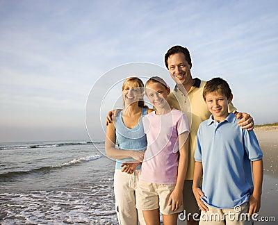 Famiglia sorridente sulla spiaggia.