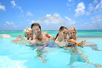 Familia alegre en piscina del infinito