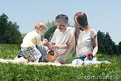 Familia alegre que merienda en el campo
